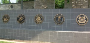 Seals of the Armed Services decorate an amphitheater stage.